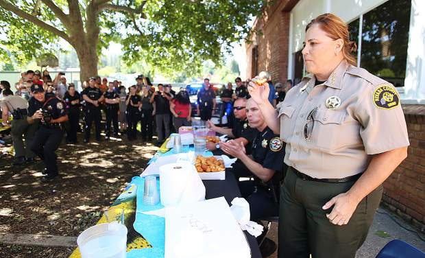 Nevada County Sheriff Shannan Moon begins eating some of the more than 100 donuts that she and her department had pledged to eat as part of the Grass Valley Charter School go fund me fundraiser established in place of the cancelled Blue Marble Jubilee.