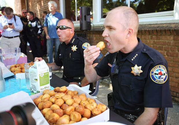 Grass Valley Chief of Police Alex Gammelgard (right) stuffs donut holes into his mouth next to Nevada City Chief of Police Chad Ellis during Thursday's donut hole challenge, a fundraiser for Grass Valley Charter School's Blue Marble Jubilee that was cancelled due to an unfounded hoax.