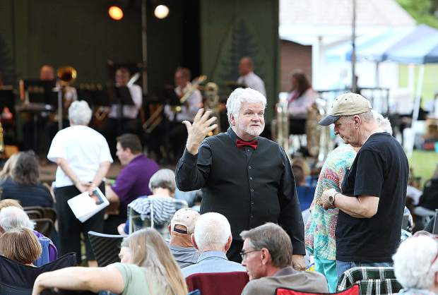 Outgoing Music in the Mountains artistic director Pete Nowlen chats with those waiting for the live brass ensemble show Tuesday evening at the Pine Tree Stage of the Nevada County Fairgrounds.