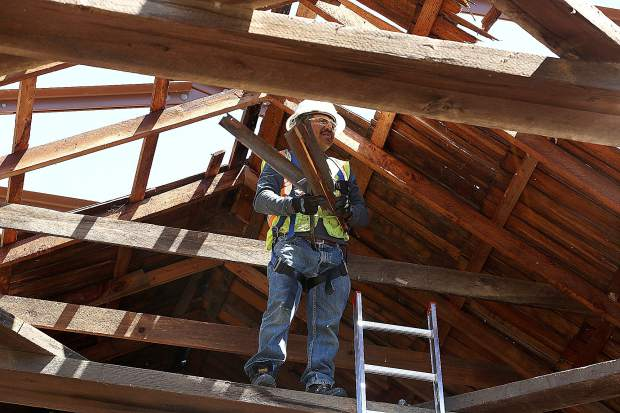 Los Angeles' Francisco Garcia works on pulling old shingles from the roof of the historic Bridgeport covered bridge Tuesday at the South Yuba River State Park where restoration work is in full swing. Workers from Spectra Historical Construction have been given a year to finish the job which entails raising the bridge 18 inches as well as replacing any damaged woodwork.