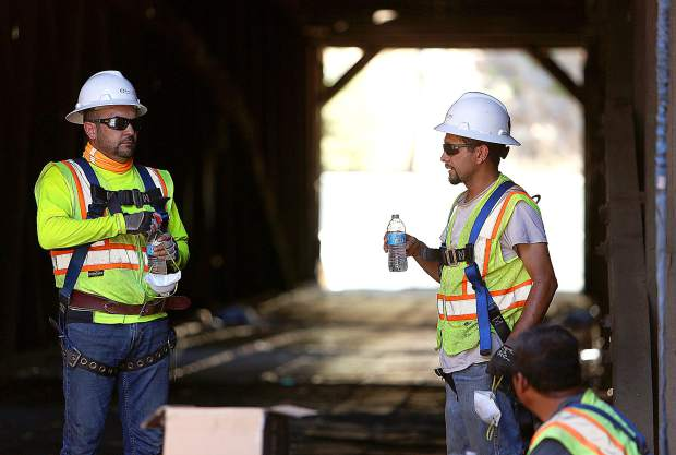 Spectra workers Luis Jesus, Rigoberto Robles and Francisco Garcia, take a break in the shade of the Bridgeport covered bridge before getting back to work removing the shingles from the structure.
