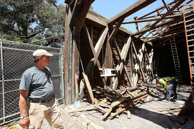 Master Bridgewright Tim Andrews from Spectra Historical Construction oversees work at the Bridgeport covered bridge Wednesday where workers are removing the old shingles from the roof of the structure.