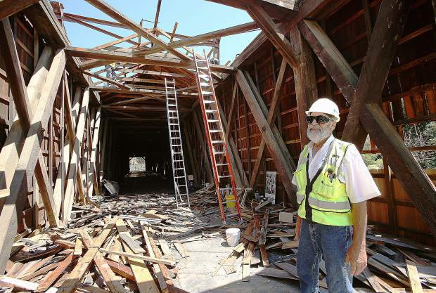 Engineer John Rebenstorff stands at the southern entrance of the Bridgeport covered bridge Wednesday morning as crews from Spectra Historical Construction work on removing the bridge's shingles. Rebenstorff, who has been contracted by State Parks, will oversee the project which contractors have been given a year to complete.