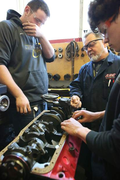 Auto shop instructor George Woodward instructs students working on a 302 Ford engine during the school year.