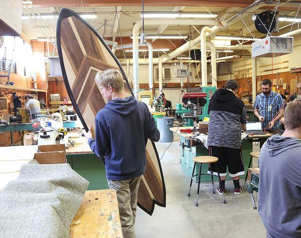 A student carries a surfboard that he made in the Nevada Union High School wood shop.