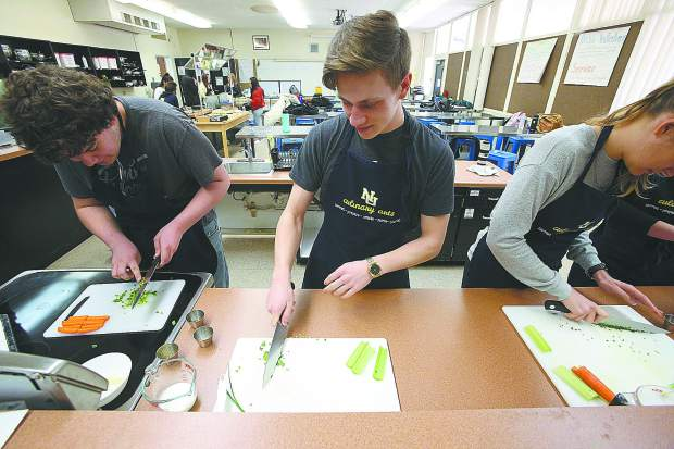 Students work on cutting vegetables during a culinary class with Kelli Morris.