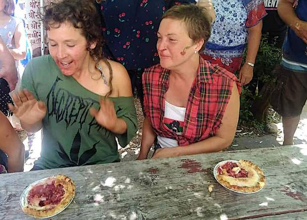 Two participants laugh as they participate in the traditonal cherry pie eating contest at this year's cherry festival.