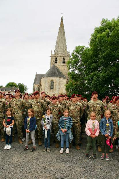 French school children and American soldiers at ceremony in Picauville, Normandy