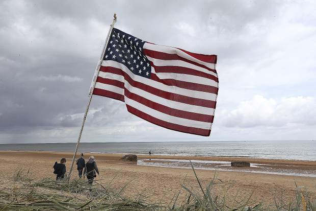 People walk on Omaha beach, Normandy, where an American flag is planted, Wednesday. Extensive commemorations are being held in the U.K. and France to honor the nearly 160,000 troops from Britain, the United States, Canada and other nations who landed in Normandy on June 6, 1944 in history's biggest amphibious invasion.
