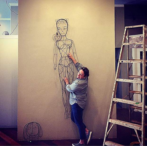A six-foot wire wall sculpture of the original 1960's Barbie, done by featured artist Richard Downs, is hung by resident Artist Sally Herring.