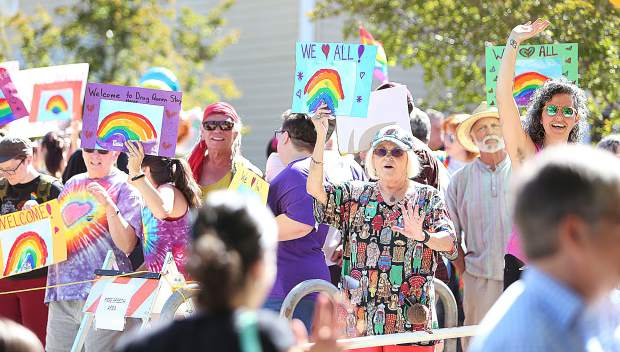 Folks gather in a free-speech area in front of the Madelyn Helling Library Ssturday morning to welcome those coming to take part in the drag queen storytime. A handful of those in opposition of the event held signs in the crowd as well.