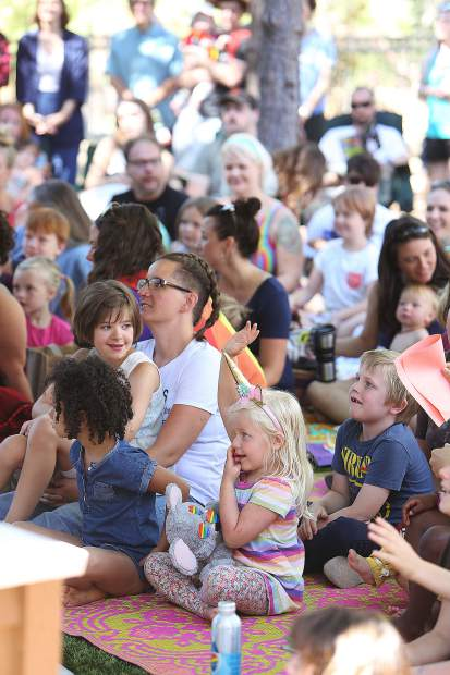 Children and their parents look on as they get ready for the story time reading Saturday morning at the Madelyn Helling Library outdoor amphitheater.