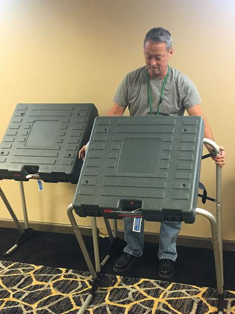 Craig McCoy, clerk-recorder assistant I, sets up a voting machine in advance of today's state Senate District 1 election.