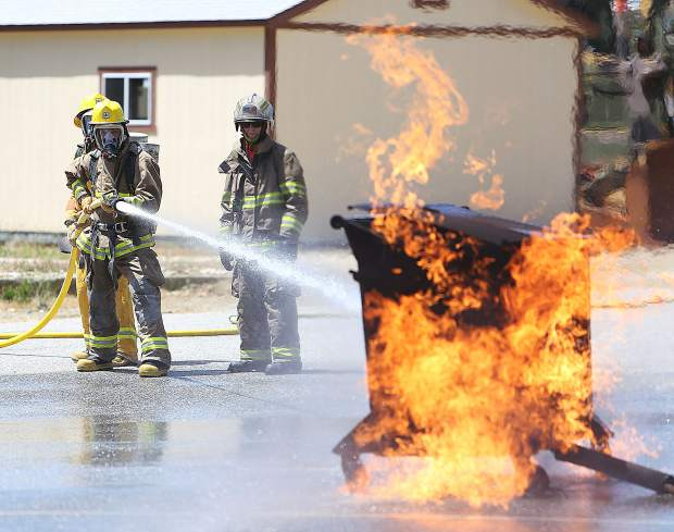 Seasonal firefighters with the Tahoe National Forest get behind the nozzle and practice extinguishing a dumpster fire while a trainer stands nearby to help during last week's training at the Grass Valley Interagency Air Attack Base.