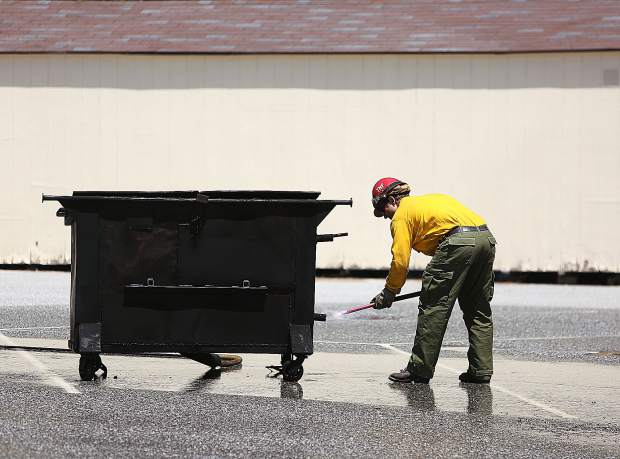 A Tahoe National Forest Firefighter places a lit flare into the bottom of the dumpster before propane gas is pumped into the container.