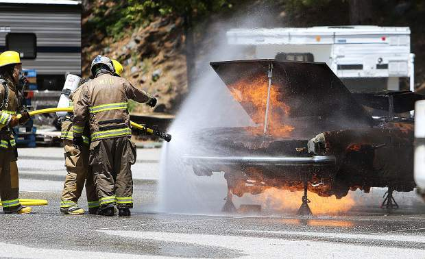 The hood of the training vehicle is propped up while seasonal Tahoe National Forest firefighters are shown the correct way to extinguish the blaze.