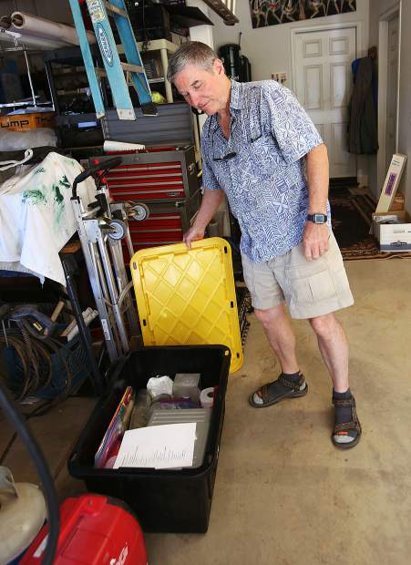 Craig Rohrson shows off a bin of important items he has stored in his garage and ready to be placed in the back of his vehicle in the case of a wildfire evacuation.