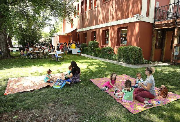 Families lay on blankets on the grass while they eat their free lunches behind the Grass Valley library Friday afternoon. The free lunches are offered to children up to 18. Adults are encouraged to bring a lunch.