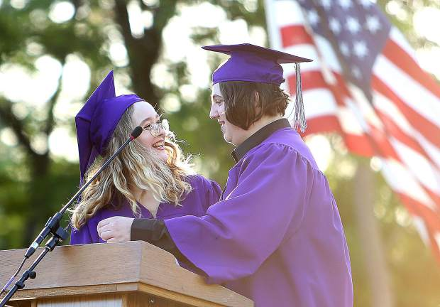 Silver Springs graduates Miles Townsend and Fiona Kierney smile at each other after delivering a speech to the crowd, school staff, and their fellow classmates during the school's graduation ceremony Thursday evening. Townsend and Kierney both graduated as juniors finishing all of their classes early to accommodate for their young child.