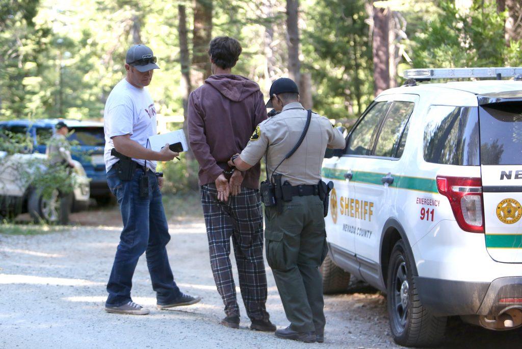 A suspect in the honey oil lab explosion is detained on scene while law enforcement conduct their investigation Wednesday morning off of Laurentian Way east of Nevada City.