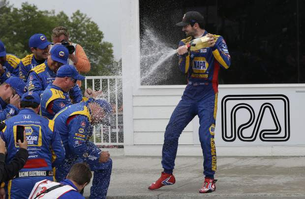 Alexander Rossi sprays champagne over his team following his win at the Rev Group Grand Prix, Sunday, June 23, 2019, at Road America in Elkhart Lake, Wis.