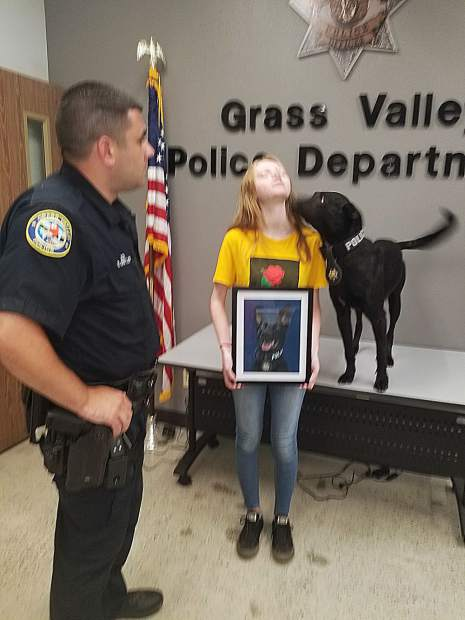 Grass Valley Police Department K9 Kano snuck a kiss from Kaydence Smith when the 14-year-old artist presented the dog's portrait to handler Evan Butler.