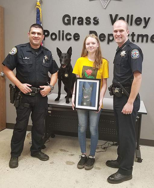 Grass Valley Police Chief Alex Gammelgard (right) asked to display the portrait of Kano at the police department. The drawing was created by 14-year-old Kaydence Smith and commissioned by K9 handler Evan Butler.
