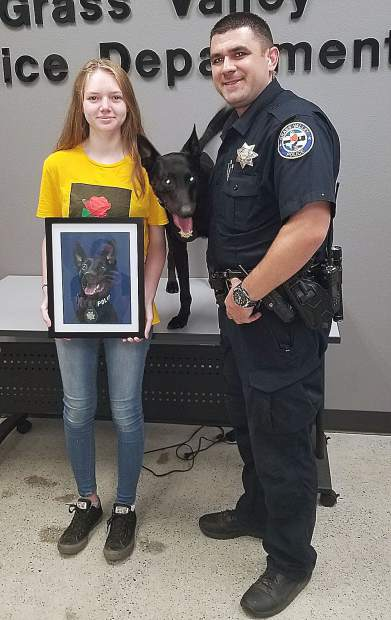Budding artist 14-year-old Kaydence Smith presented a portrait of Grass Valley Police Department K9 officer Kano to his handler, Evan Butler.