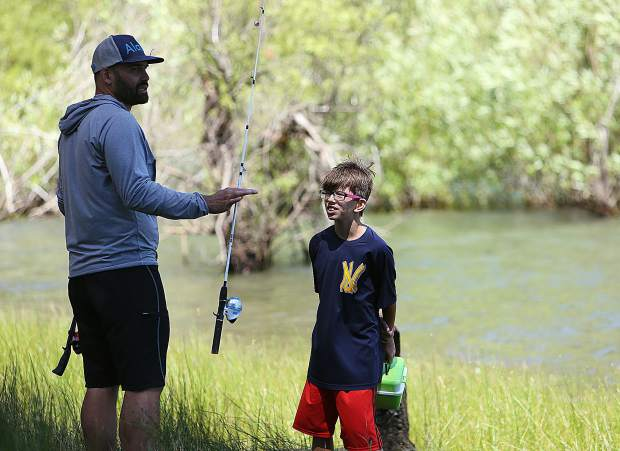 Extended School Year coordinator Brendan Cariaga helps student Caleb Nowell with a little fishing action on Scotts Flat Lake Wednesday afternoon.