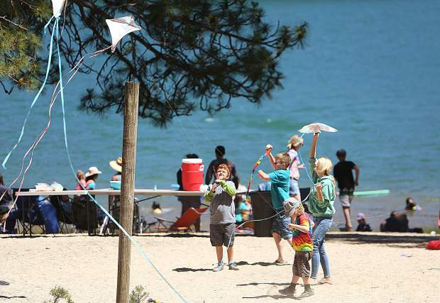 Special education students fly kites along at Scotts Flat Lake while others play in the water during a summer campout for students with individualized education plans.