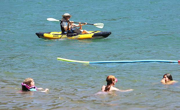 A pair of kayakers pass by a group of swimmers on the shore of Scotts Flat Lake Wednesday afternoon. Students had the opportunity to participate in activities such as flying kites, fishing, kayaking, swimming and many more during their summer campout.