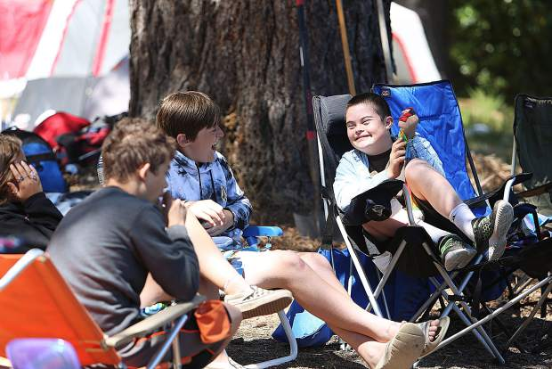Cypress Werderitsch smiles with his friends while sitting lakeside during the extended school year's campout for students with individualized education programs.