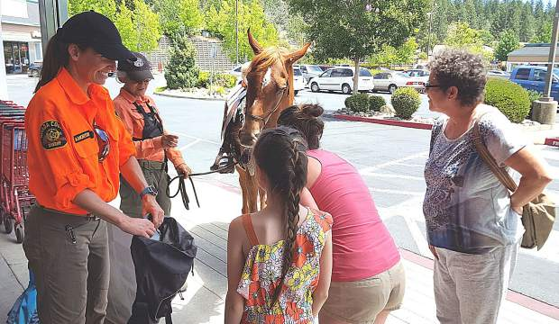 "The Nevada County Sheriff's Search & Rescue team will stage its annual fundraiser, ""Stuff the Pack,"" July 6 at local shopping centers. At last year's event, SAR member Anna Morton accepted donations from SaveMart shoppers while SAR member Cathy Scott and her horse Mandy shared their gratitude."