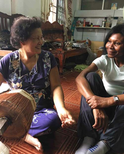 Eno Jonah of Nzuri Textiles, right, chats with a basketmaker in Thailand.