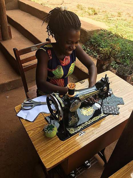 Ruth, a local  Batwa, trained in tailoring through the Kellermann Foundation's Batwa Development Program, creates a Day for Girls kit on one of two newly donated sewing machines.