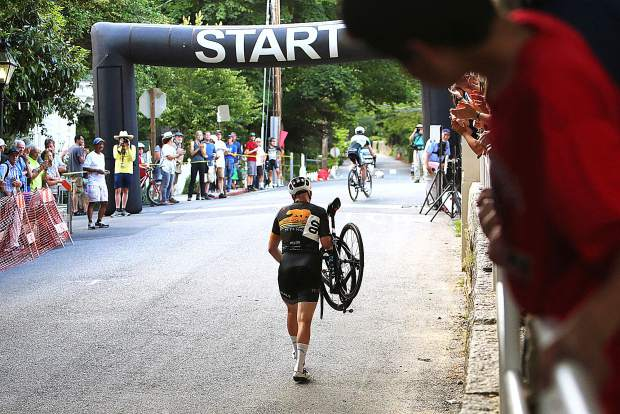 A Nevada City Classic bicycle racer is forced to walk his bike across the finish line following a late race crash that decided the fate for many in the men's pro race June 2.