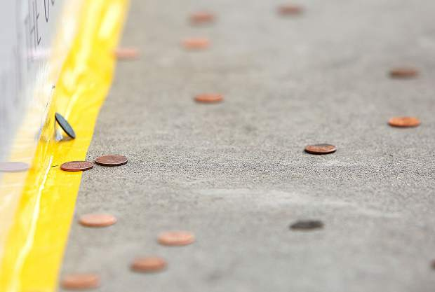 Members of the public warm up with their spare pennies during the annual John Kane Penny Pitch held on the sidewalk in front of Kane's restaurant in downtown Grass Valley Saturday afternoon.