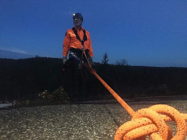 Nevada County Sheriff's Search & Rescue volunteer Ken Taylor prepares to be lowered during a night ops training at the White Cloud helipad.