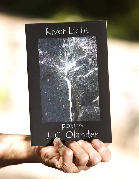 Olander holds a copy of his book