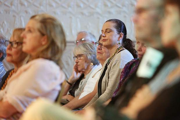 Poetry fans close their eyes as they take in the spoken prose of the renowned poets selected to read during Friday night's Community of Writers scholarship fund event. All proceeds from the ticket and book sales benefit the scholarship fund.