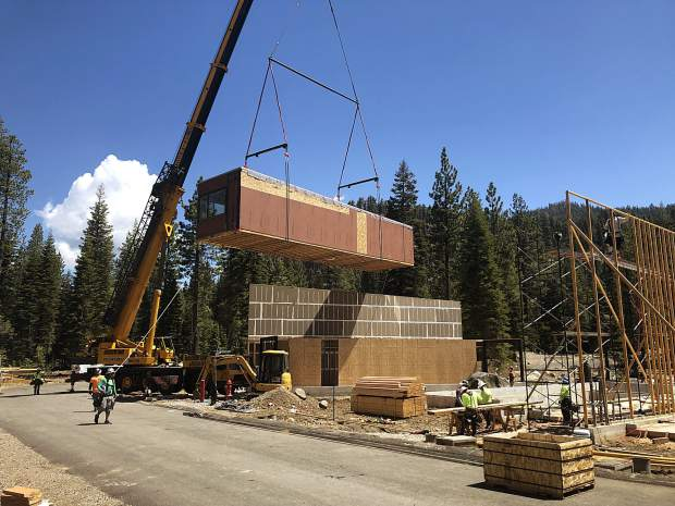 One of six modules, which later formed a new duplex, is lowered into place in Olympic Valley.