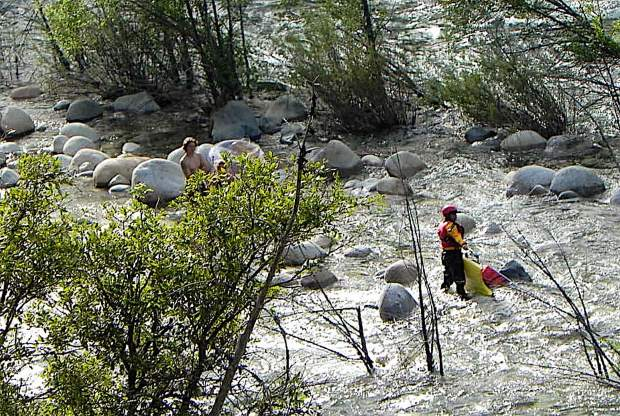 A couple stranded on a rock in the middle of the Yuba River await rescue by firefighters Sunday.