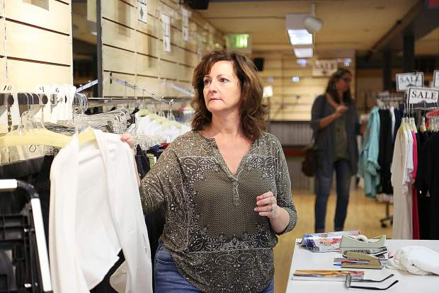 Swarthout places clothing items on the rack during business hours Tuesday afternoon at her downtown Grass Valley shop, Mill Street Clothing Co.