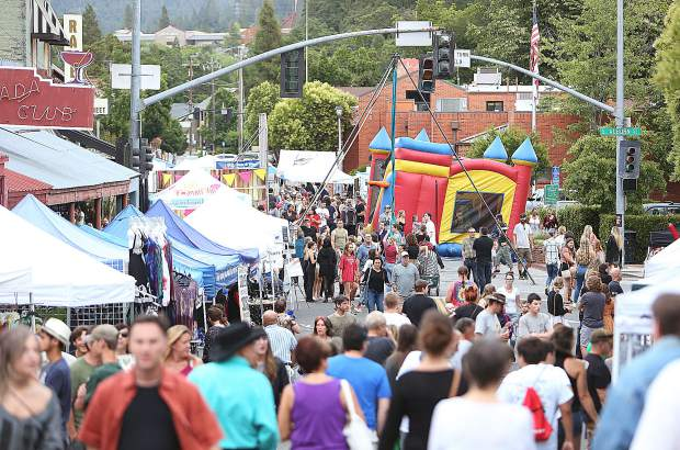 Hundreds of community members take to the streets during the inaugural Thursday Night Market of the summer season taking in everything from vendor booths, fresh fruit and flowers, as well as food, entertainment, and a bounce house for the kids.