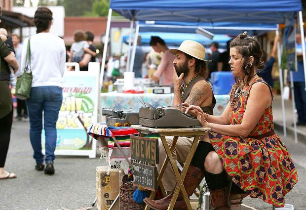 Jesse and Camile work their typewriters at their Poem Store where folks get to name their topic and name your price during Thursday evening's Thursday Night Market.