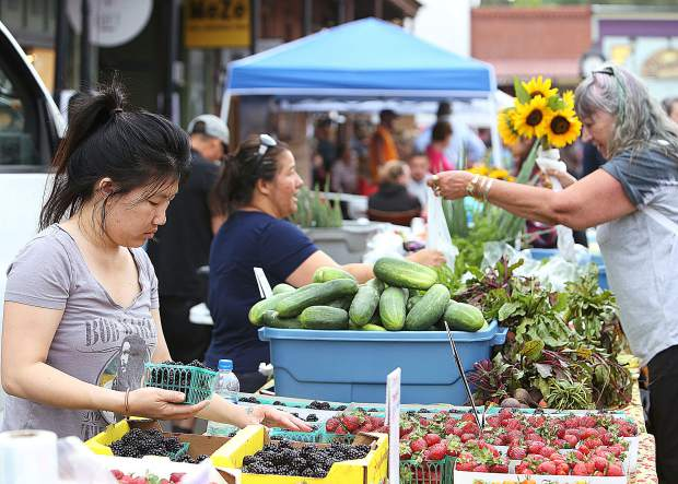 Marysville's Lucy Xiong helps to fill baskets of fruit for Xiong Family Farm out of Sutter during Thursday's inaugural Thursday Night Market for the 2019 summer.