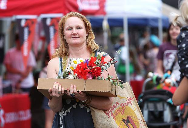 A Thursday Night Market shopper carriers her find of fresh flowers during Thursday's inaugural event of the 2019 summer.