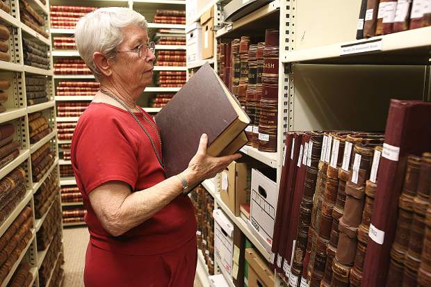 Searls Library director Pat Chesnut finds a place for the donated volumes of The Western Slopes Connection on the shelves at the library and are now available for public viewing.
