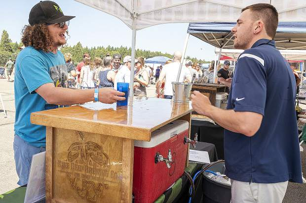 Justin Holtz-Knee, right, pours beer for Kevin Souza, left, at the Grass Valley Airshow and Brewfest.