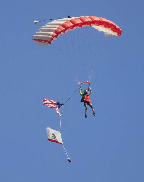 A member of the SkyDance SkyDiving of Yolo County parachuting with two other team members at the opening ceremonies of the Grass Valley Airshow.